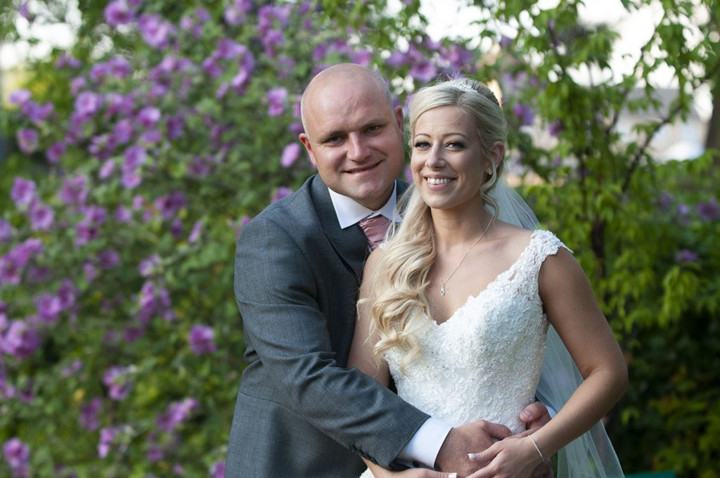 Leicester Wedding Photography happy couple in front of lilac flowers on wedding day, bride, groom