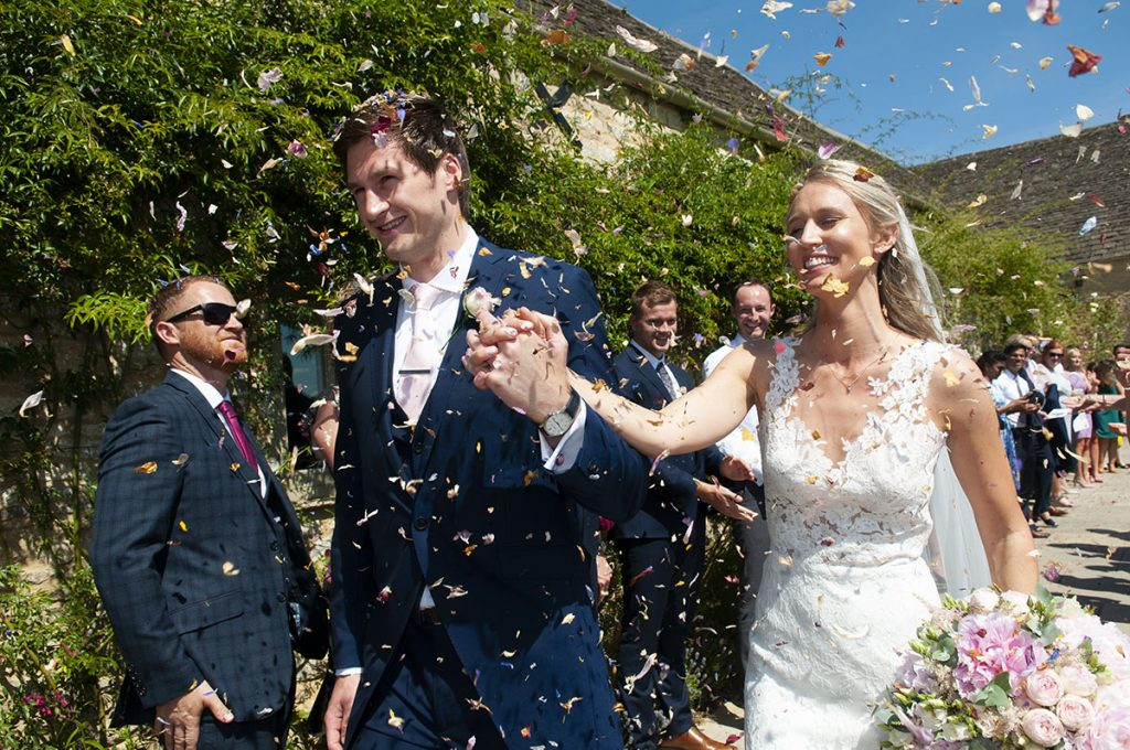 fun couple confetti Leicester Wedding Photographer bride and groom hold hands