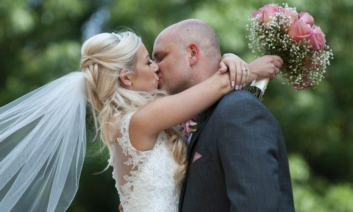 bride and groom kiss on wedding day Leicester wedding photographer Rose Tinted Photos Birstall fun couple, huge hug, rose bouquet, veil