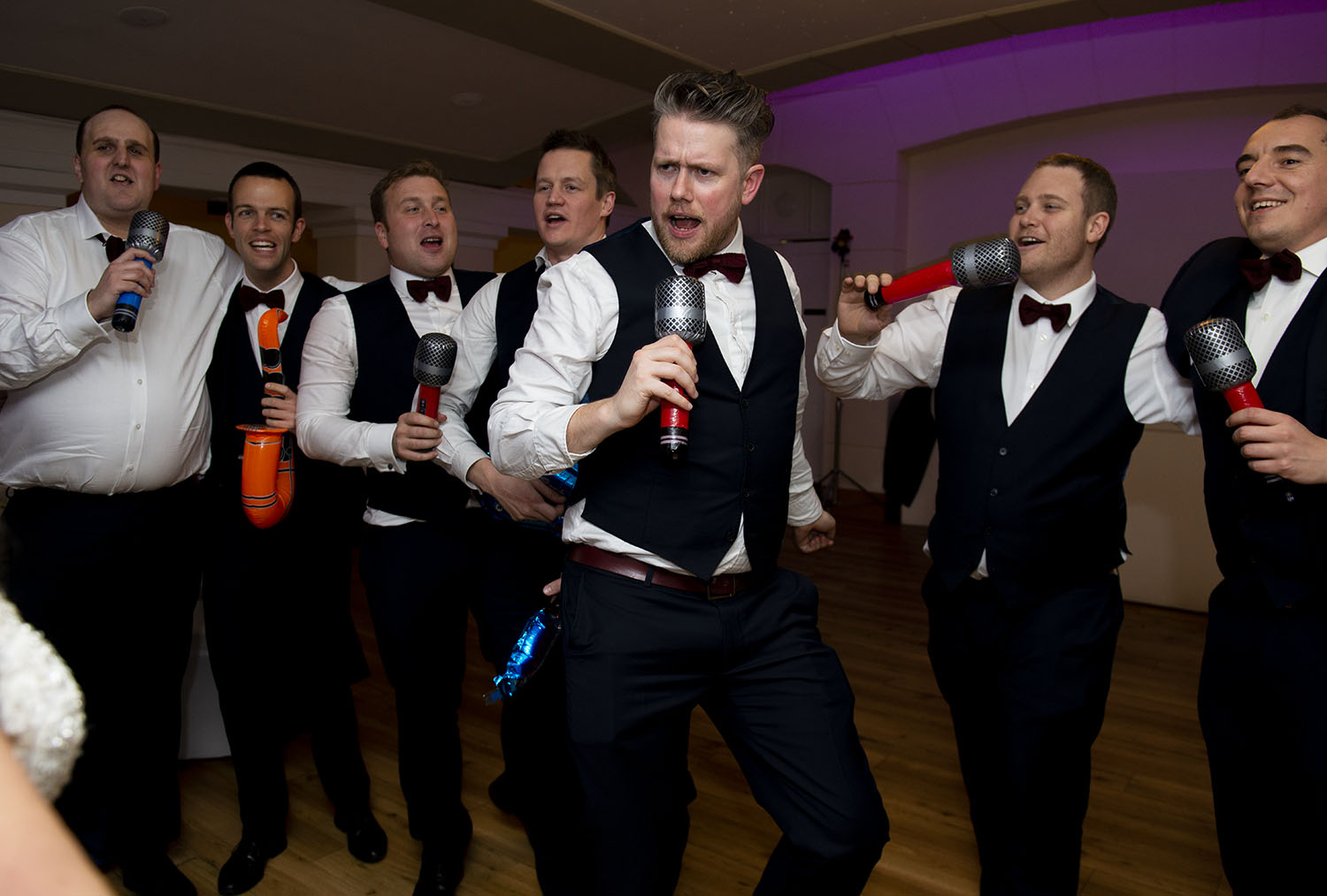 Leicester WEdding photographer, groom sings into blow up microphone, groomsmen