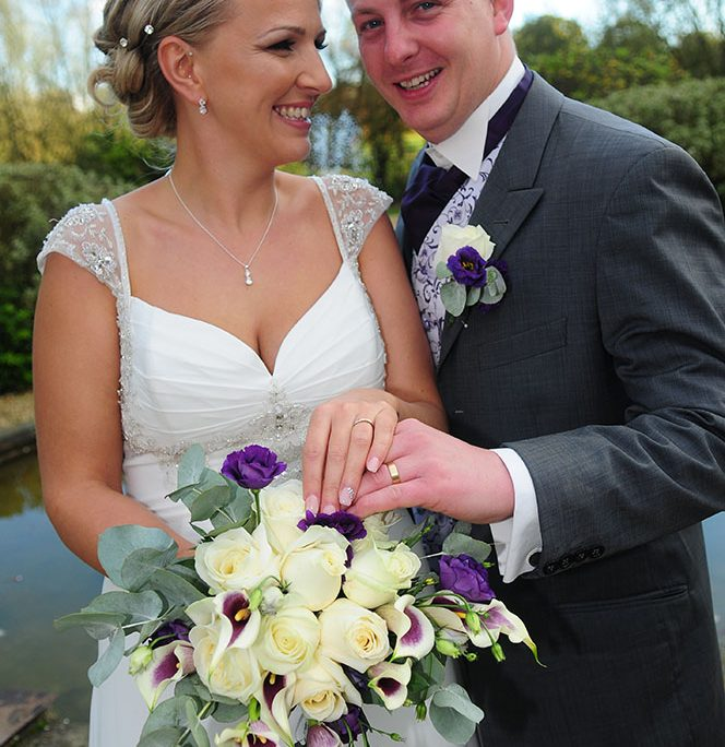 happy couple on Autumn wedding day showing rings