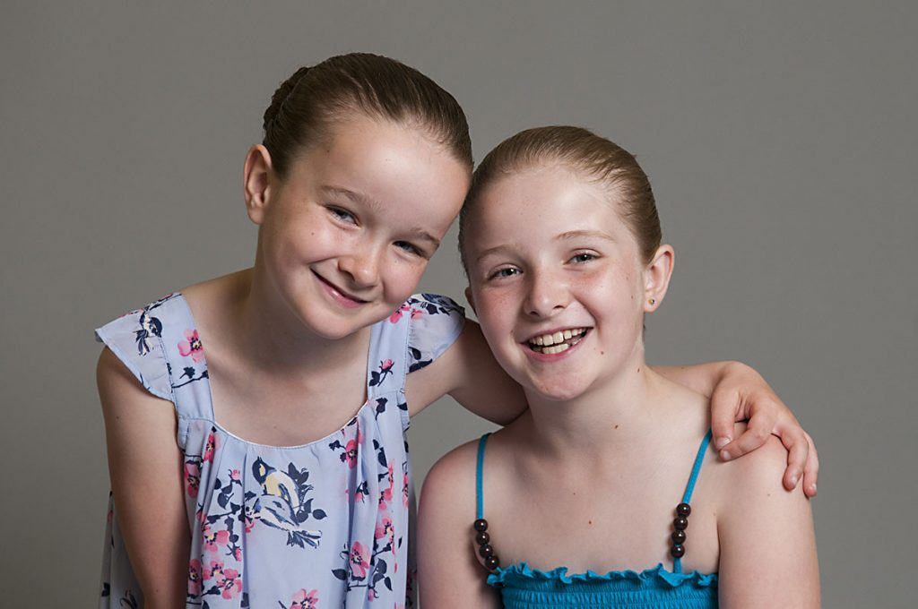 smiling sisters portrait by Rose Tinted Photos Leicester photography studio, Birstall