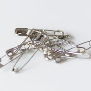 pile of safety pins on white background. product photography, leicestershire photographer
