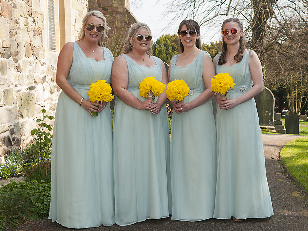 cool bridesmaids in sunglasses and turquoise dresses with daffodil bouquets
