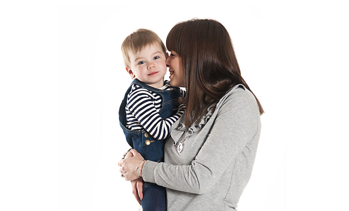 Family photographs, mother holding her toddler and snuggling her cheek, studio photograph, birstall, leicestershire