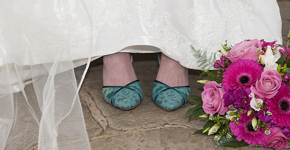 blue shoes peeping out from under a white wedding dress at Quorn Grange Hotel In Leicestershire