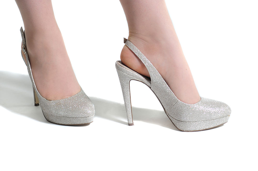 silver sparkle high heeled slingback shoes worn in a Leicester studio on white background