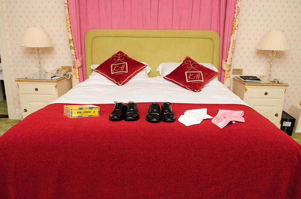 Kilworth House Hotel bed with cigars, groom and best man shoes and cravats laid out, Leicestershire wedding