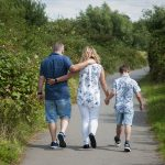 family hold hands on a walk through Watermead Country Park, Birstall, Thurmaston, Leicestershire