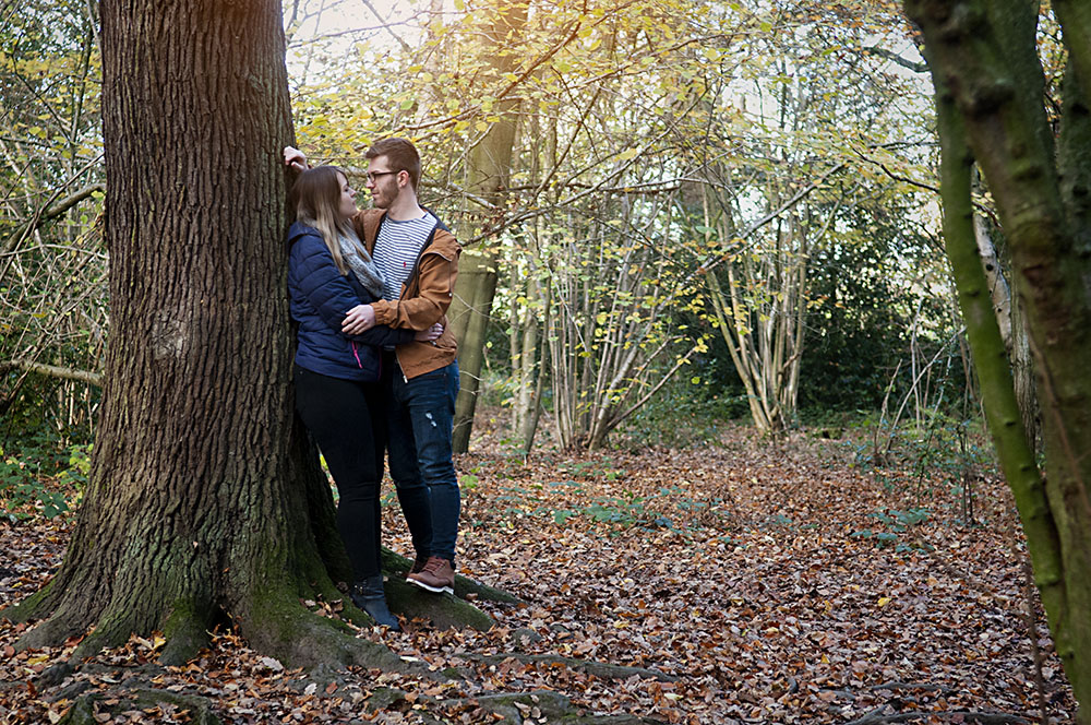 romantic couple rest against a tree in Autumn at Swithland Woods