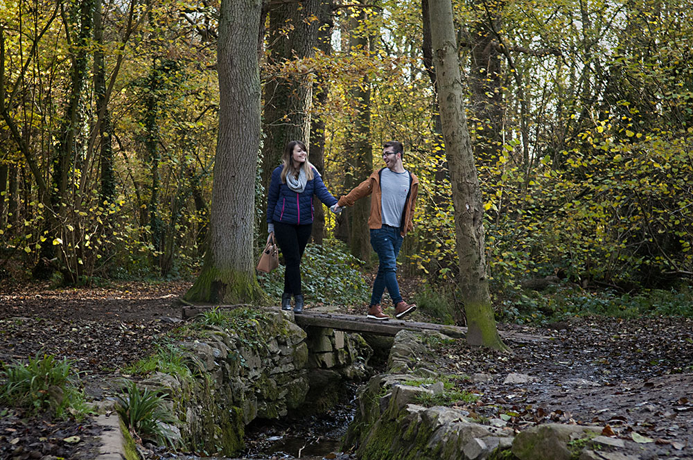 Engaged couple cross a bridge hand in hand at Swithland Woods, wedding photography