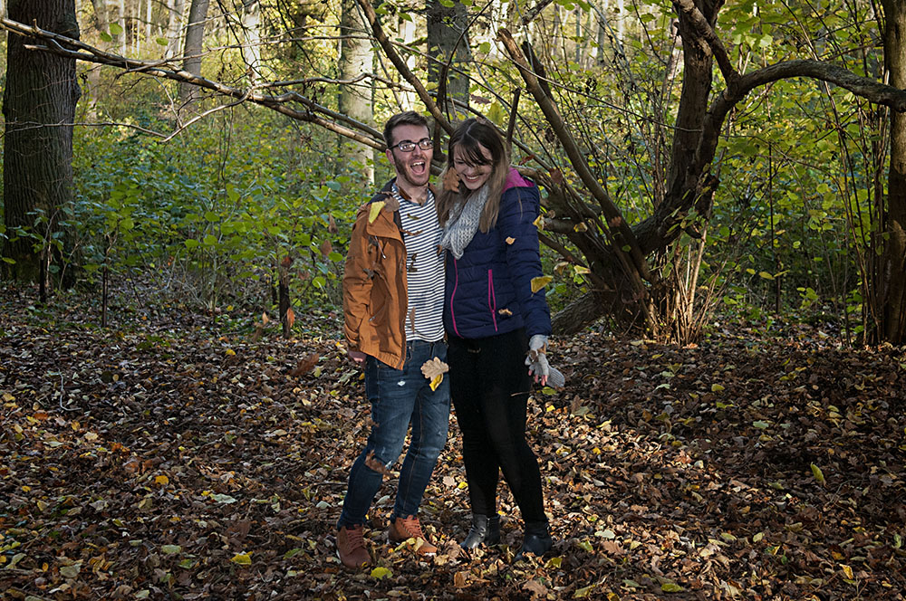 couple laughing as they throw autumn leaves around, engagement photoshoot, Leicester