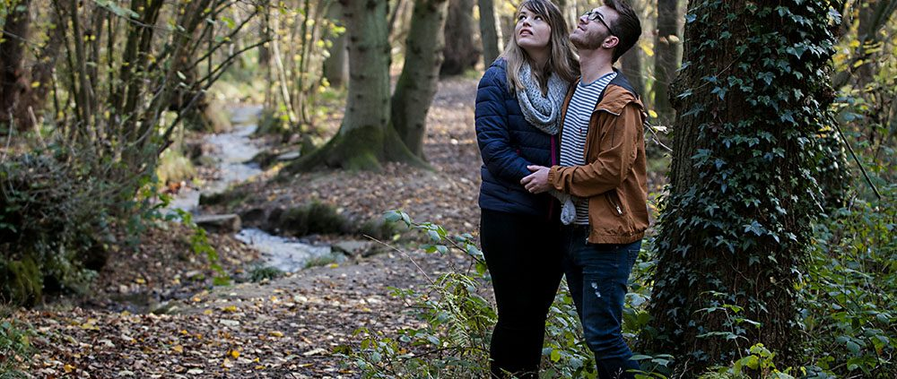 couple gaze into the trees above whilst holding one another, set amongst the fallen autumn leaves and flowing streams of Swithland Woods, Leicestershire