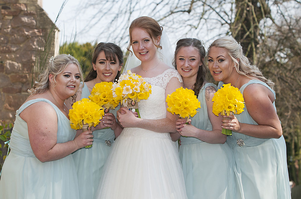 Bride and four bridesmaids in aqua dresses with daffodil bouquets