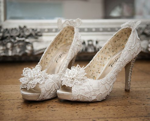 stunning lace covered bridal shoes photographed in front of elegant mirror by Leicester wedding photographer Rose Tinted Photos