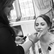 how to wed like a Royal in Leicestershire, bride having make up done in gown lipstick brush black and white