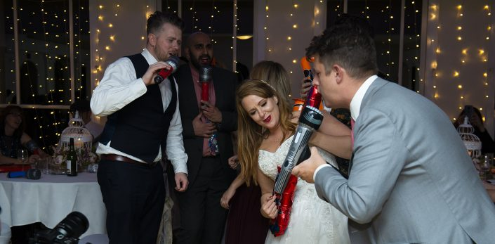 Leicester wedding photographer bride and groom sing and have fun with inflatable microphone and guitar