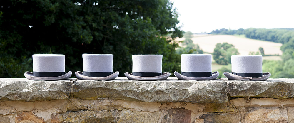 five grey top hats sitting on a wall, countryside background, leicester wedding photographer, Rose Tinted Photos
