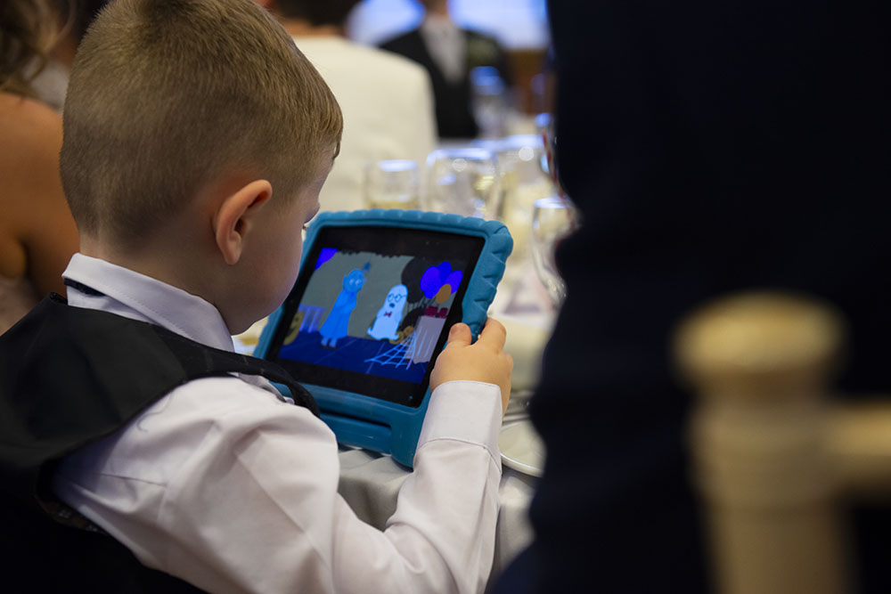 child watches telly on tablet during wedding speeches rose tinted photos