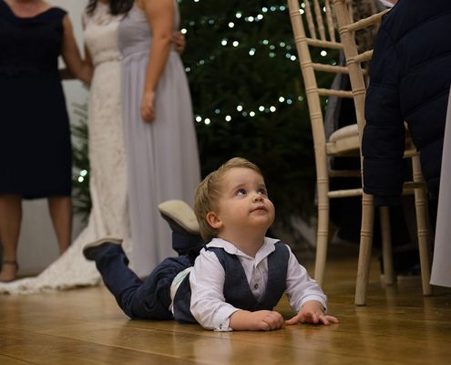 children at weddings on the floor while bride has photo behind