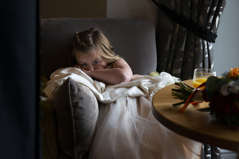 flower girl takes a break from the wedding chaos in beautiful window light