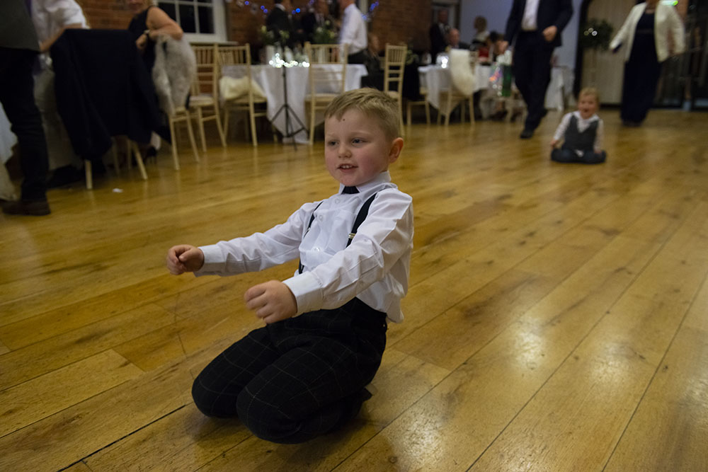 child slides across dancefloor on his knees at a wedding rose tinted photos