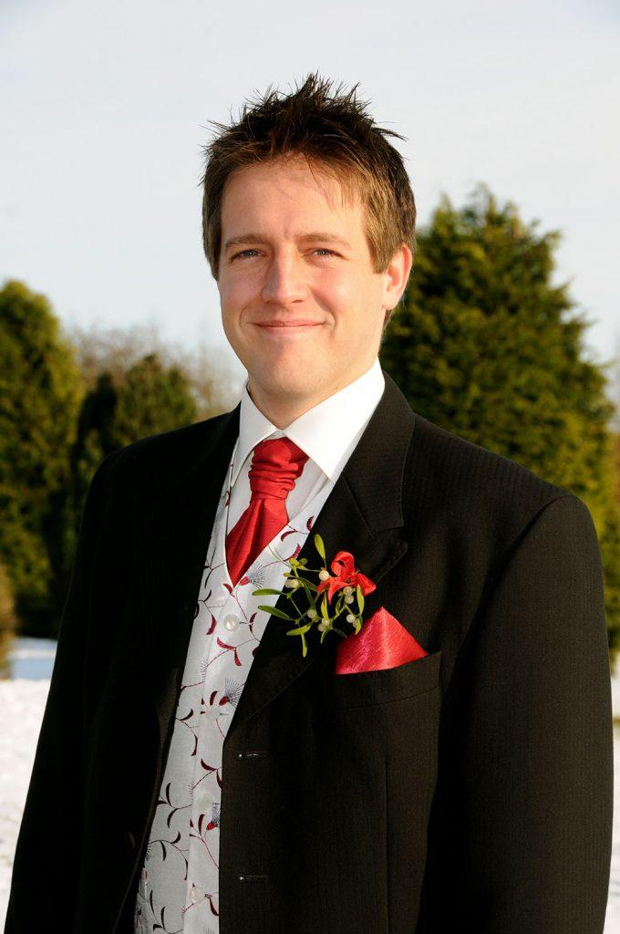 Groom on snowy wedding day, mistletoe buttonhole, Christmas wedding