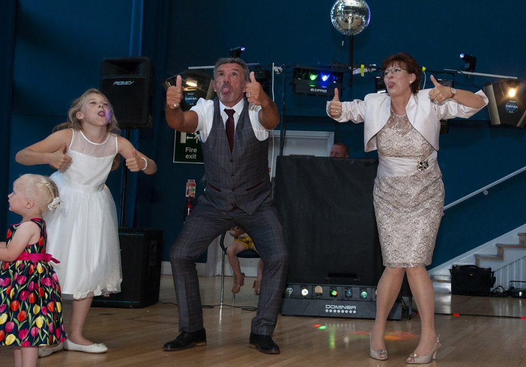 mother of the bride and step-father of the bride on dancefloor with bridesmaid, silly dance, thumbs up, bums out, tongues out, chi chi wah, melton wedding photography