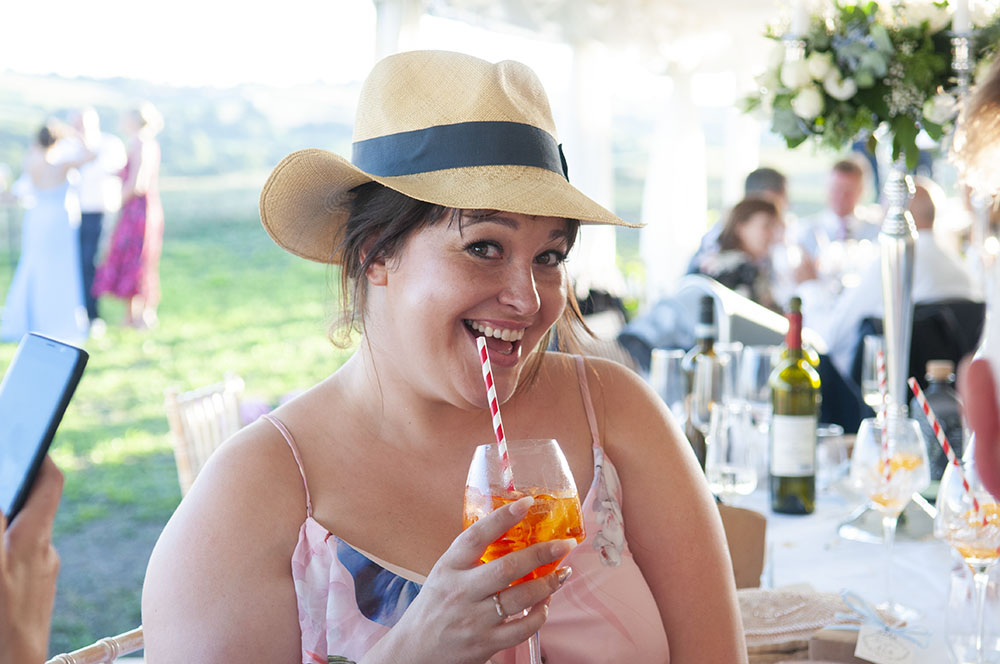 wedding guest in funky sunhat drinking asperol, leicester wedding photographer