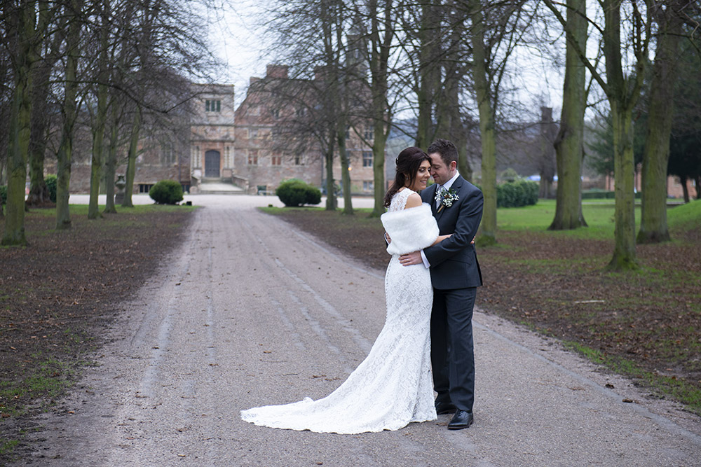 leicestershire wedding photography bride and groom embrace in front of country house ruins, winter wedding