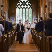 married couple walk down aisle hand in hand after church wedding ceremony bride groom bouquet leicester wedding photography