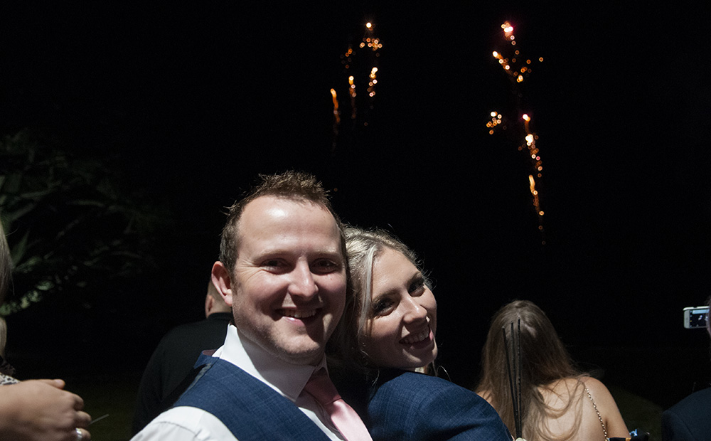 best man and bridesmaid couple enjoy wedding day firework display loving romantic